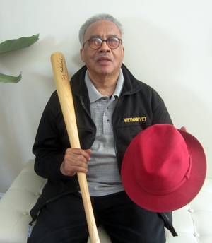 Vietnam veteran Abraham Bunkley, Duty's nephew, shows his uncle's autographed bat and trademark red fedora.
