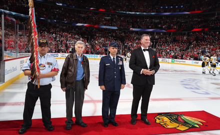 Herman Sitrick (second from left) is honored during the National Anthem, sung by Jim Cornelison (right), before the Blackhawks season opener Oct. 5. A retired Air Force lieutenant general (to Sitrick's left) also participated as old Army corporal Sitrick was remembered for his astounding Battle of the Bulge heroics (Photo courtesy Chicago Blackhawks).